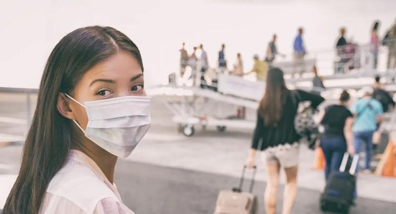 Femme avec un masque devant un avion