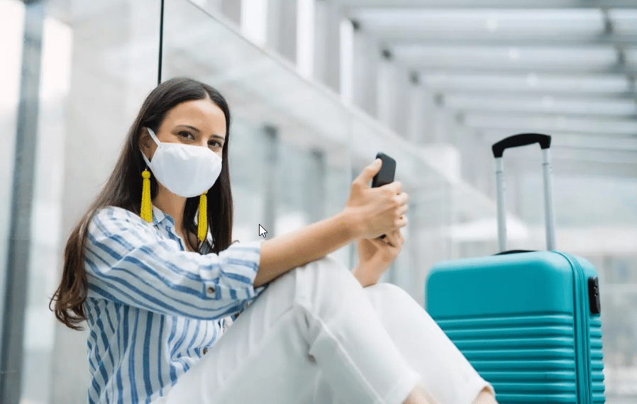 Une femme portant un masque avec une valise